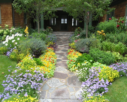 cobblestone walkway leading to home, surrounded by beautiful landscaping