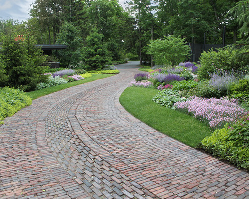 brick and stone path to home surrounded by beautiful landscaping
