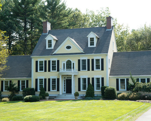 classic home with soft yellow shade and black shutters