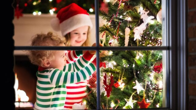 children placing ornaments on a christmas tree
