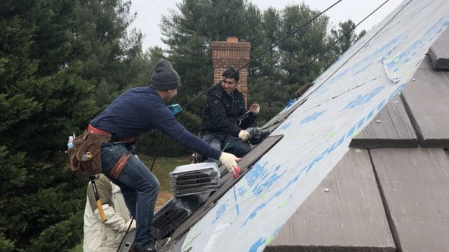 workers installing a composite roof on a home